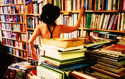 A woman reaches for a book in a second-hand bookshop, wearing only a black hat and tie.